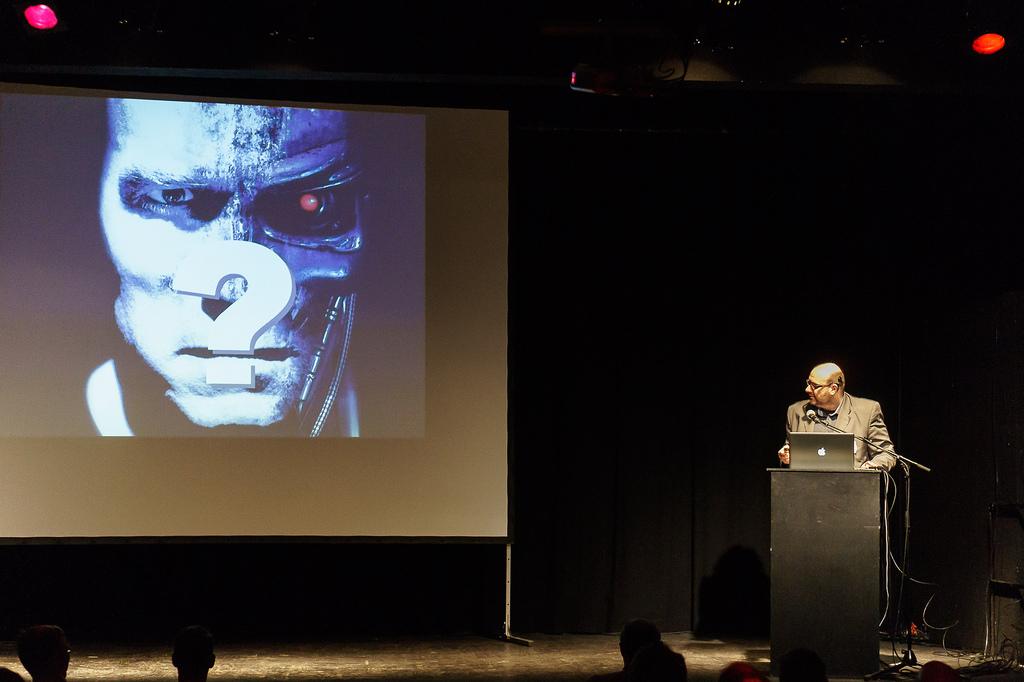 Enno Park am Rednerpult. Auf der Leinwand das Bild eines Cyborgs.